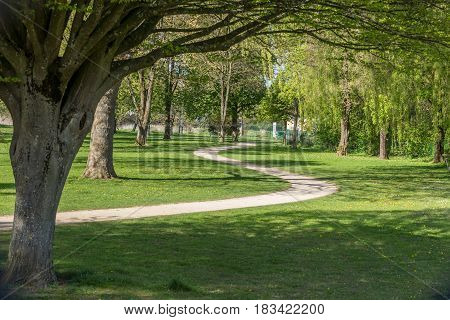 Sinuous Path On An Idyllic Spring European Park With Green Lawn And Beautiful Old Trees
