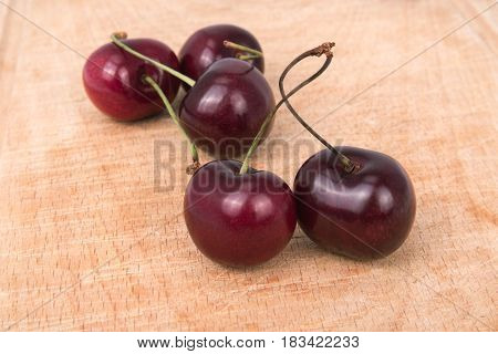 red cherries close-up on a wooden board