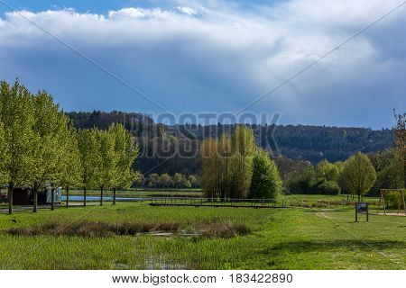 Small Bridge Crossing The Encounter Of A River And A Lake On A Small Park In Europe. Trees And Fores