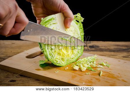 cabbage cutting with kitchen knife on wooden board, isolated on black background