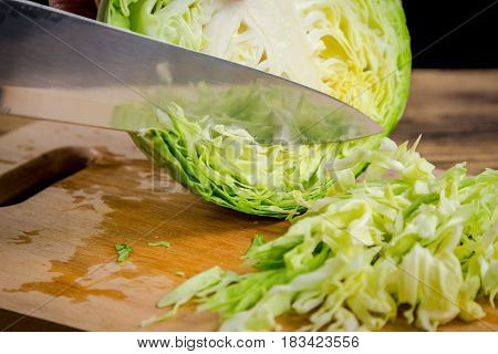 Slicing cabbage with kitchen knife on wooden board, isolated on black background
