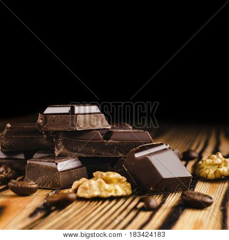 Pieces of bitter dark chocolate cubes on heap walnut core and coffee bean on wooden background close-up view.