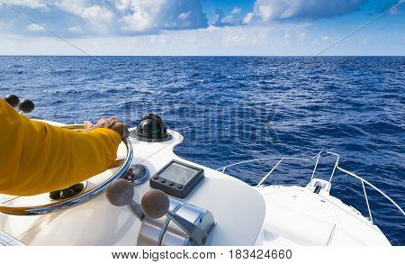 Hand of captain on steering wheel of motor boat in the blue ocean