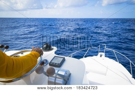 Hand of captain on steering wheel of motor boat in the blue ocean