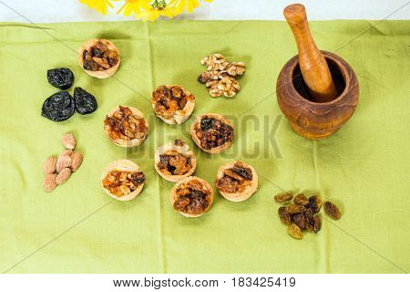 Professional baking. Portioned shortbread baskets with filling of nuts and dried fruits. Background wooden mortar with pestle