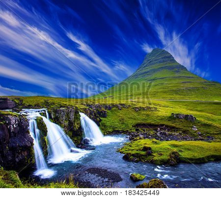 The most famous mountain in Iceland is Kirkufell. Cirrus clouds in the blue sky. At the foot of the mountain cascading waterfalls Kirkjoufellfoss. The concept of exotic and extreme tourism