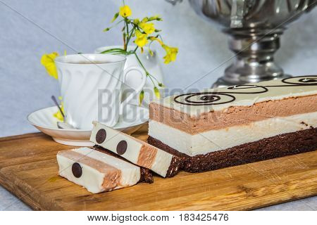 Professional bakery. Three-layer chocolate cake, decorated with chocolate patterns. Beautiful cake Three-colate. Background - white vase with flowers and porcelain cup with hot tea