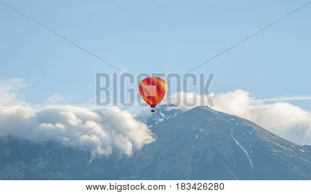 colorful air ballon aerostat flying over clouds and mountains