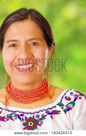 Closeup beautiful hispanic woman wearing traditional andean white blouse with colorful decoration around neck, matching red necklace and ear, posing happily for camera, garden background.