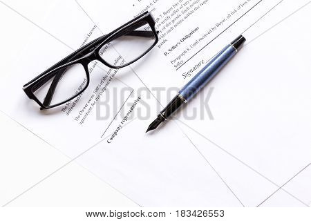 Signing the contract with pen and glasses in business work on office desk background top view