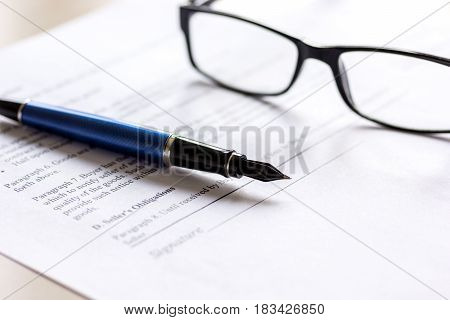 Feather pen and glasses lying on signed documents on office desk