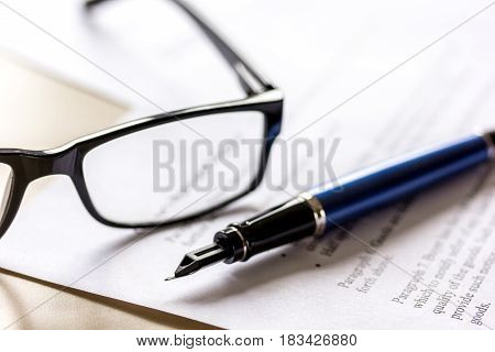 Signing the contract with pen and glasses in business work on office desk background
