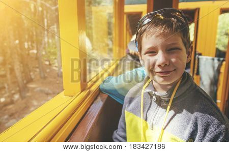 Happy boy on a train in the summer