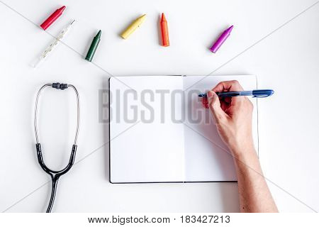 stethoscope, copybook and hands on children doctor's office desk background top view mockup