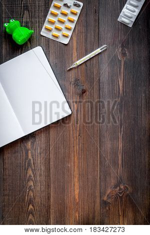 Pediatrician workplace with stethoscope and notebook on wooden table background top view mockup