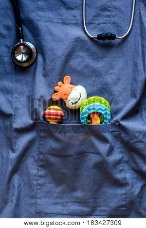 Pediatrics pocket with children toys on blue fabric background top view space for text