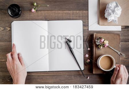 writer tools with coffee and hands in profession concept on wooden desk background top view