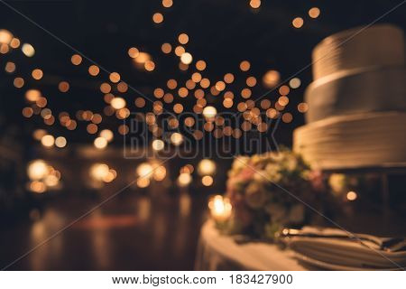 Wedding party evening. Blurred dance floor and wedding cake. Wedding invitation background.