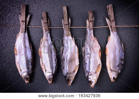 Dried fish stew hanging on clothespins on a rope abstract background