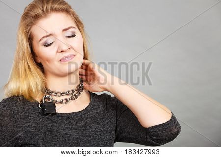 Slavery medical concept. Unhappy woman having chain around neck sore throat problem.