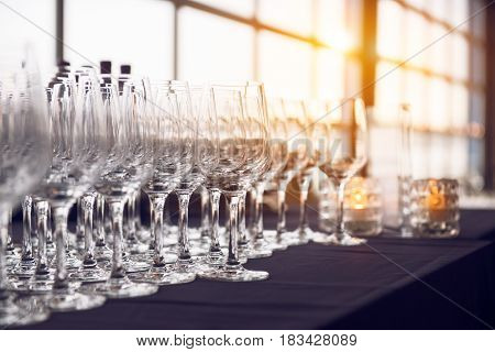 Empty wine glasses in the row in the bar before evening party and dinner.