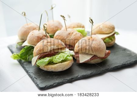 Mini sandwiches with salad cheese bacon and salami on stone plate.
