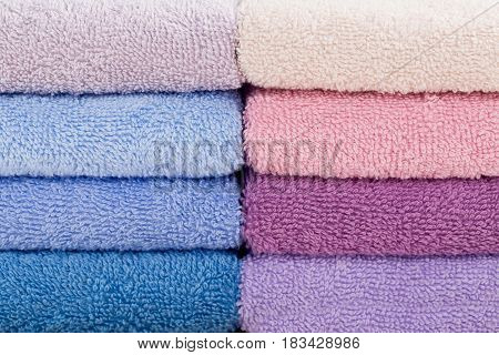 Stack of colorful bath towels on light background. Pastel colors cotton towels. Hygiene fabricspa and textile concept. Close up