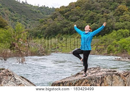 Young Girl Stretching on Rocks Near Fast River