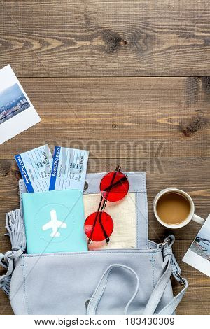 tourist lifestyle with bag, flight tickets and passport on wooden table background top view mockup