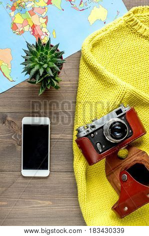vacation concept with traveller outfit mobile, world map and camera on wooden desk background top view