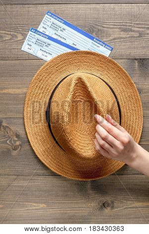 tourist lifestyle with flight tickets and hat in a hand on wooden table background top view