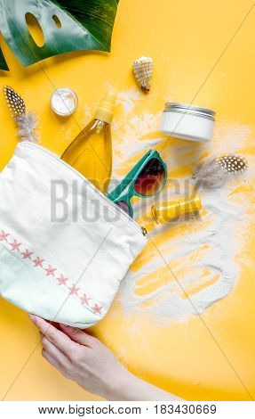 Summer cosmetic set for woman with protection cream and lotion and sunglasses on orange background top view