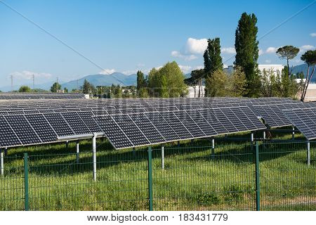 Solar panels multitude on green field blue sky mountainous background