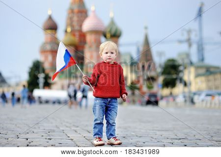 Cute Boy Holding Russian Flag With Vasilevsky Descent On Background