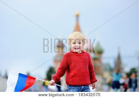 Cute Boy Holding Russian Flag With And Vasilevsky Descent On Background