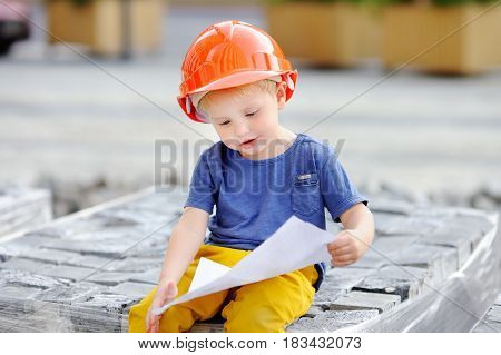 Little Builder In Hardhats Reading Construction Drawing