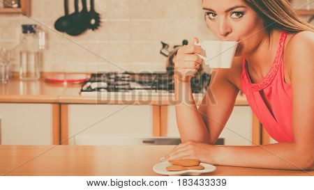 Pretty woman with heart shape gingerbread cookies drinking tea or coffee at home. Gorgeous young girl with hot beverage relaxing in kitchen.