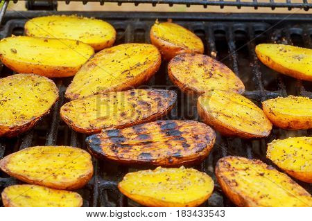 Big Slice Of Village-style Potatoes On Hot Bbq Charcoal Grill. Flames Of Fire In The Background.