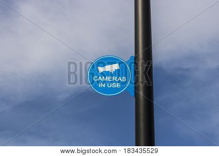 Blue Security Camera In Use Sign on Black Post and Partly Sunny Background IV