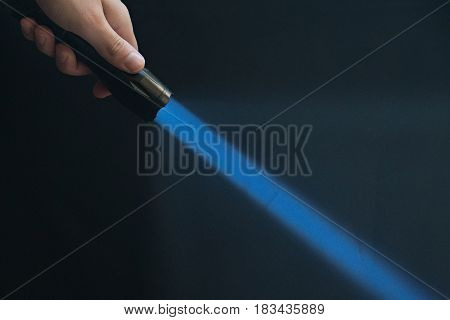 Led Flashlight With Blue Beam Light In The Man's Hand From The Upper Left Corner Of The Frame.