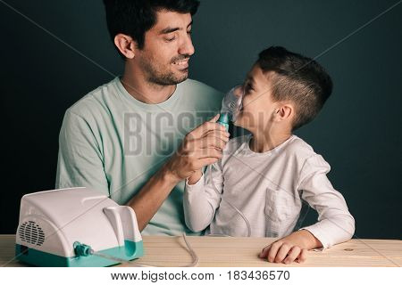 Portrait Of Father And Son Using Domestic Inhaler / Nebulizer