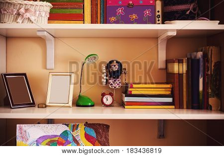 Closeup view on child's shelf with toys books and things that children use.