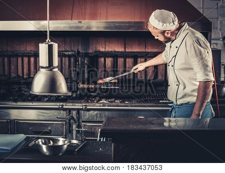 Food concept. Young chef in white uniform monitors the degree of roasting and turns meat with the forceps in interior of modern restaurant kitchen. Preparing traditional beef steak on barbecue oven