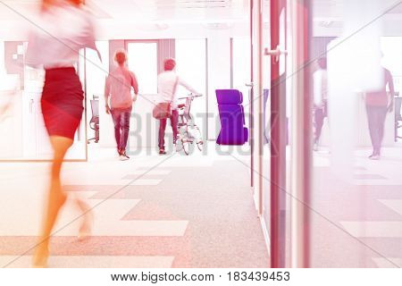 Blurred motion of businesswoman walking with male colleagues in background at office