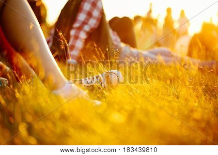 Legs in sport shoes or sneakers in grass. summer lifestyle. Colorful warm yellow toning. People on holiday laying on ground. recreation in park nature. Music Festival outdoors.