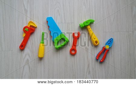 Colorful plastic tools on gray wood background