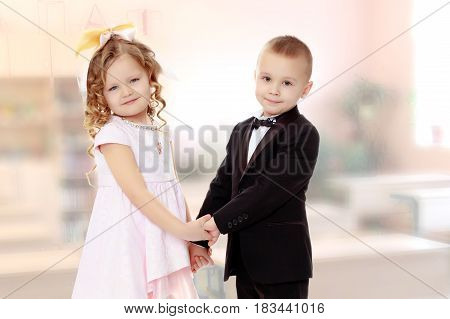 Cute little boy and girl holding hands.In the Montessori room the children's garden where there are shelves with toys and material.