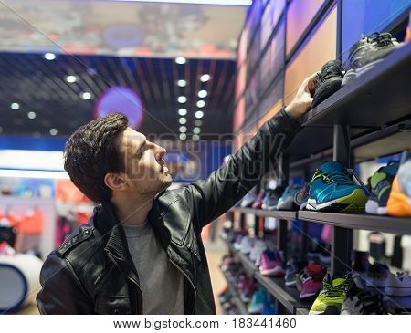 portrait of young male customer choosing black sneakers at supermarket store. He is taking shoes from upper shelf