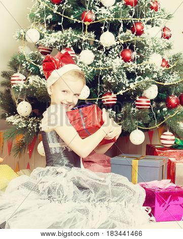 Beautiful little girl in a dress of Princess around the Christmas tree.She sits beside the Christmas tree with a big gift.Creative toning of a photograph.