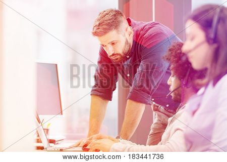 Mid adult businessman using laptop with colleagues wearing headsets in office